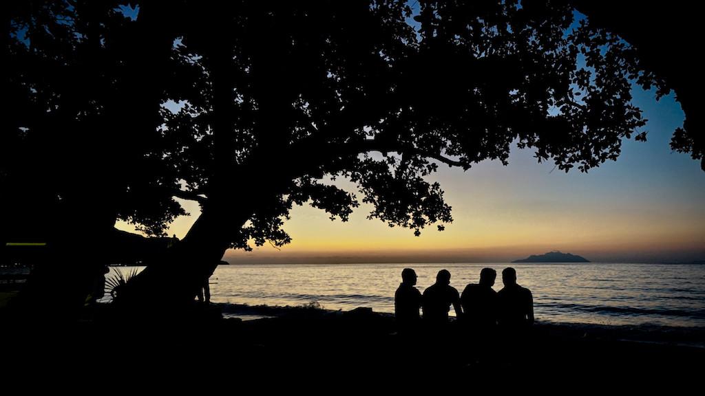 Menschen im Gegenlicht der Abenddämmerung am Strand von Beau Vallon