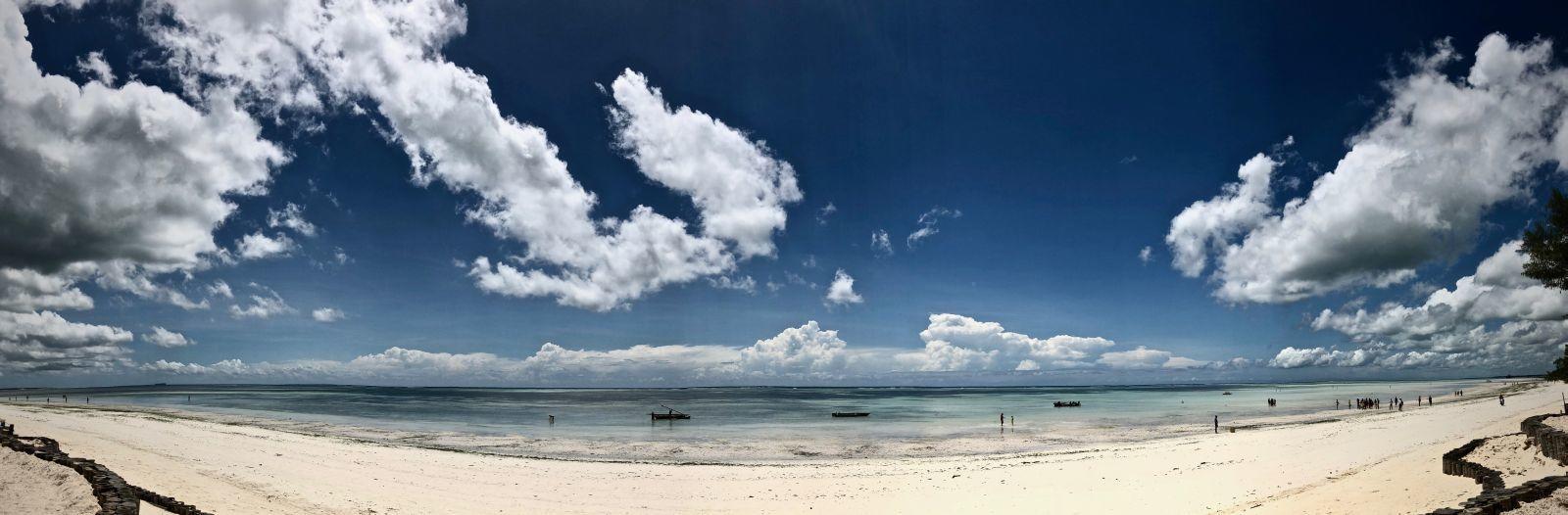 Weißer Sand und türkisfarbenes Meer unter tiefblauem Himmel am Strand von Kiwengwa.