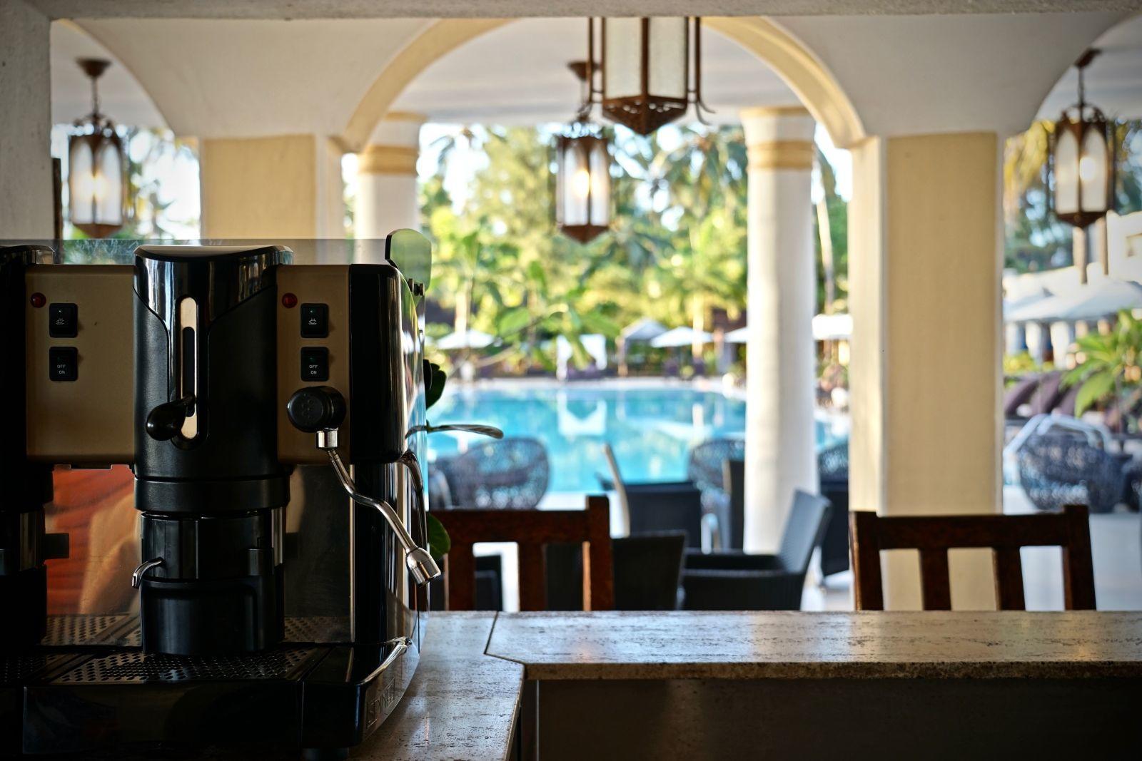 Komfortzone im Schatten von Palmen: Latte Macchiato am Pool.