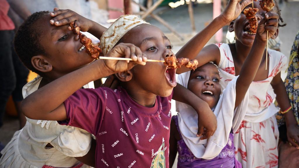 Südlich von Kiwengwa freuen sich diese Kinder über gegrillte Hähnchenspieße.