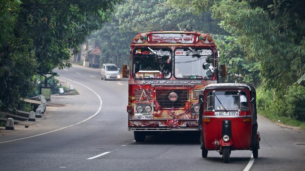 Überlandbus überholt Tuk-Tuk auf der Straße von Colombo nach Kandy, Sri Lanka